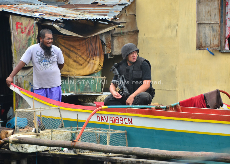 DAVAO. A member of the Special Weapons and Tactics team keep a tight watch on the coastline as the team led by Davao City Police Office Dir. Ronald dela Rosa enter the slums of Barangay Ilang to visit suspected drug pushers Monday. (Seth delos Reyes)