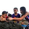 DAVAO. Gitabangan sa mga dagko pagtabon ang lawas sa gamay nga bata sa baybayon sa pantalan sa Sta. Ana, dakbayan sa Davao sa ilang paglingaw-lingaw samtang nangaligo kagahapon sa buntag. (Seth Delos Reyes)