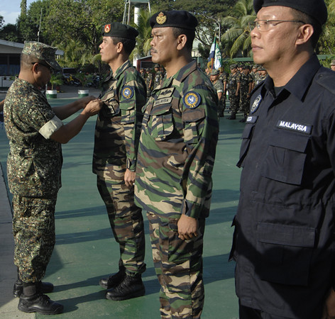 ZAMBOANGA. A photo handout shows Wesmincom deputy commander Brig. Gen. Eugenio Clemen pinning Bronze Cross Medals to IMT Team Site 3 members at Camp Basilio Navarro. (Bong Garcia)