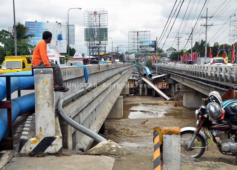 DAVAO. Trabahante sa Department of Public Works and Highways nagbantay sa tubig sa Davao River ubos sa Generoso Bridge nga padayong mitaas kagahapon sa buntag. (Seth delos Reyes)