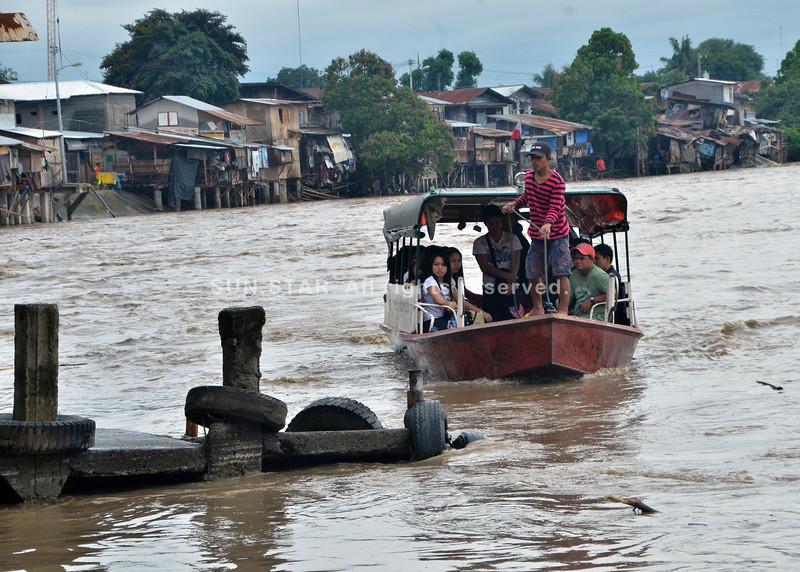DAVAO. Kusog ang sulog sa Davao River tungod sa kanunay nga pag-uwan, apan padayon ang biyahe sa mga banka patabok sa SIR Phase 1, siyudad sa sa Davao. Mobati og kahadlok ang uban, apan mosakay gihapon kay mas makadaginot sila sa pamasahe. (Seth delos Reyes)