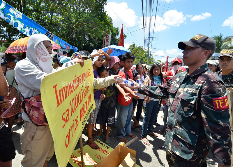 DAVAO. After the chaos, protesters still holding a placard stating their demand, is handed a bottle of water by a member of the Task Force Davao along D. Suazo Street yesterday. (King Rodriguez)