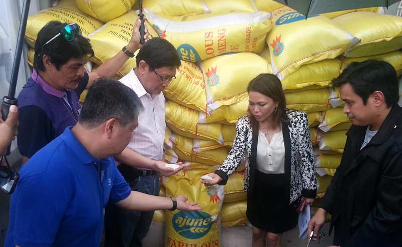 CAGAYAN DE ORO. Customs officials led by Danilo Lim (in white polo) and Lourdes Mangaoang (2nd from right) inspect the smuggled Vietnamese rice loaded in 10 container vans inside the sub-port of Mindanao Container Terminal in Tagoloan, Misamis Oriental. (Joey P. Nacalaban)