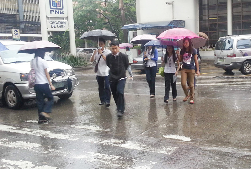 "CAGAYAN DE ORO. Students brave through heavy rains poured by ""Crising"" on Tuesday as the storm battered several provinces in Mindanao. Classes went on as normal in all levels in Cagayan de Oro Tuesday. (Joey P. Nacalaban)"