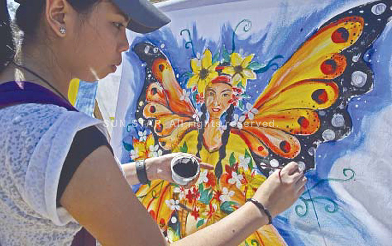 """BAGUIO. Jane Marsha of the Baguio Arts Guild is in the zone as she paints her materpiece during the """"Let the Flower Blooms"""" painting contest at the Melvin Jones Grandstand. The event is part of the long month celebration of Panagbenga. More than 50 joined the flower painting contest. (Photo by Mauricio Victa)"""