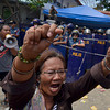 DAVAO. A woman shouts for mercy while holding a rosary as the angry mob who barged into the Department of Social Welfare and Development 11 office is dispersed by policemen with truncheons and shields. (King Rodriguez)