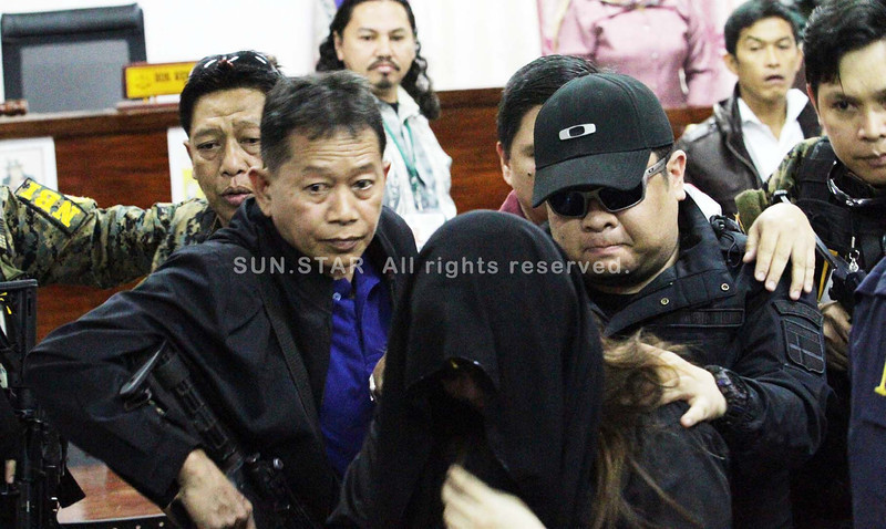 "The National Bureau of Investigation closely guards Jachob ""Coco"" Rasuman and his wife, Princess, during the arraignment in three Regional Trial Courts in the cities of Marawi and Iligan on Tuesday. The couple faces syndicated estafa charges involving the multi-million investment scam. (Photo by Richel V. Umel of Sun.Star Cagayan de Oro)"