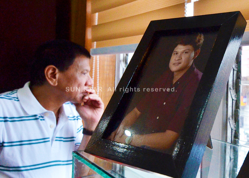 DAVAO. City Mayor Rodrigo Duterte peers at the window close to a photo frame of his son, Vice Mayor Paolo, inside his office, Monday afternoon. Paulo recently warned delinquent real property owners to pay their obligations and inefficient tax collectors to improve their performance. (King Rodriguez)