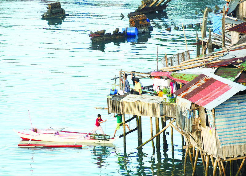 "LIVING BY THE SEA. Residents of Sitio Paradise, Barangay Looc, Mandaue City dock their boat in their ""backyard"" after a leisurely outing at the Mactan Channel.  (Sun.Star Photo/Allan Cuizon)"