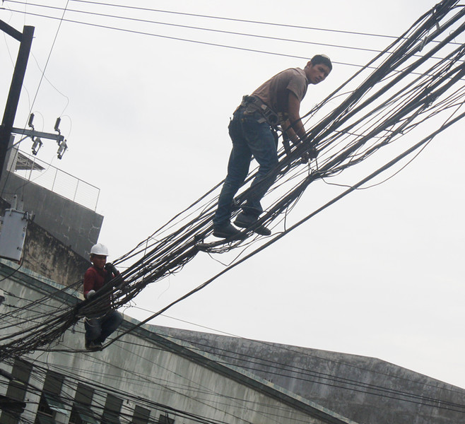 Even if dangerous, linemen make their way out every day to rid the city of spaghetti wires. (Joey P. Nacalaban)