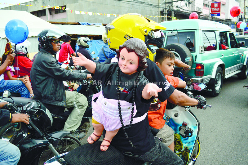 SAFE AND SECURE. While other devotees hold their Sto. Nino images aloft, a participant of the Traslacion believes it is safer for him and his son to strap the icon while he drives his motorbike. Story on A1. (Sun.Star Photo/Alan Tangcawan)