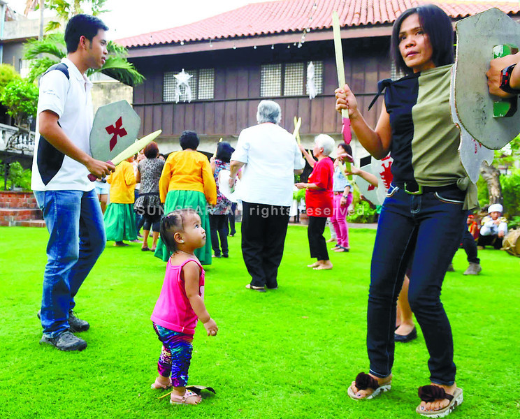 PRAYER DANCE. A toddler tries to imitate a woman who is doing the sinug, the traditional prayer dance offering for Sto. Nino. At the background is the historical Casa Gorordo. (Sun.Star Photo/Arni Aclao)