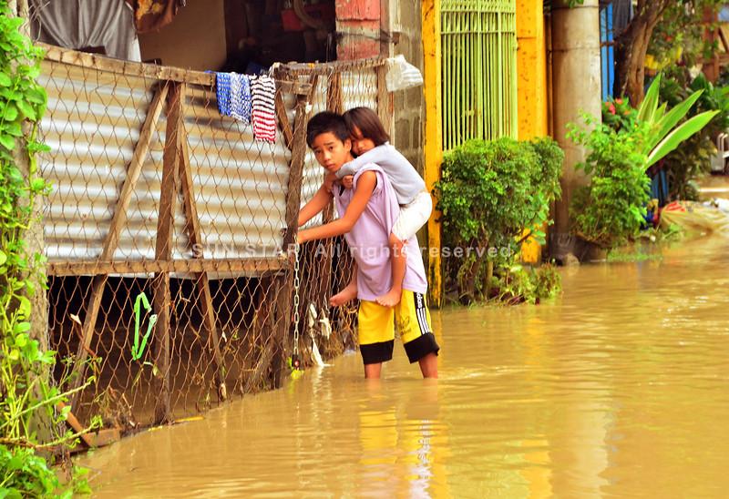 DAVAO. Gibaba sa lalaki ang iyang manghud pagawas sa ilang balay duol sa simbahan sa Iglesia ni Cristo sa Bunawan, siyudad sa Davao. (Seth Delos Reyes)