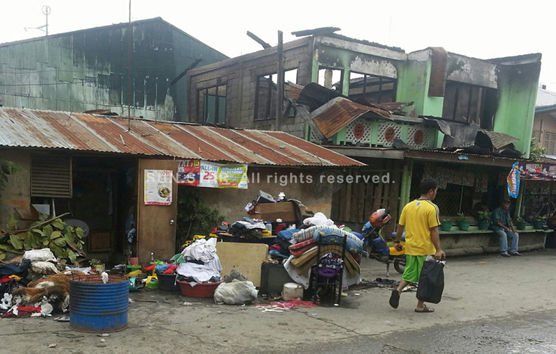 SOME residents manage to gather their personal belongings when a fire broke out in Barangay 36 on Tuesday dawn. The fire damaged at least P600,000 worth of property and affected around 76 individuals. (Joey P. Nacalaban)
