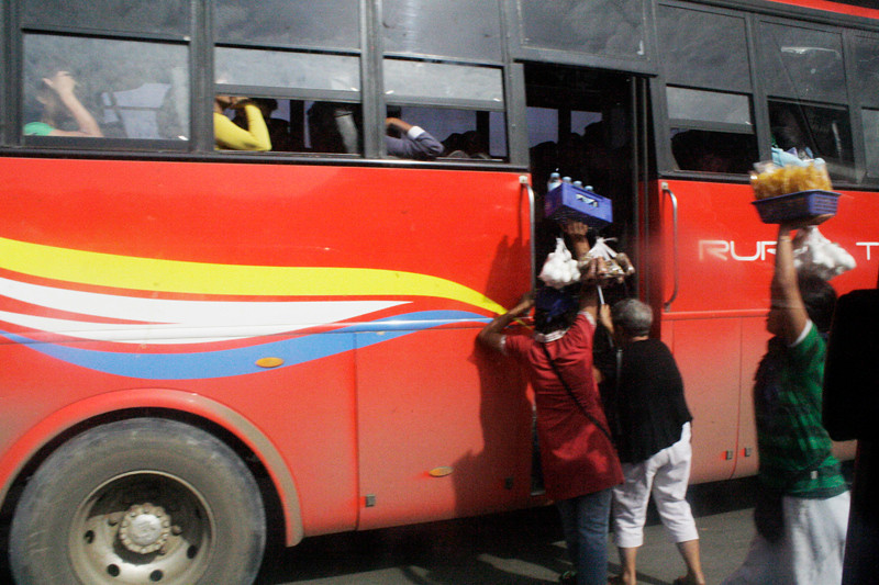 Ambulant vendors try to attract the attention of bus passengers in an effort to earn more while the bus makes a stop in a terminal in Barangay Puerto. (Joey P. Nacalaban)