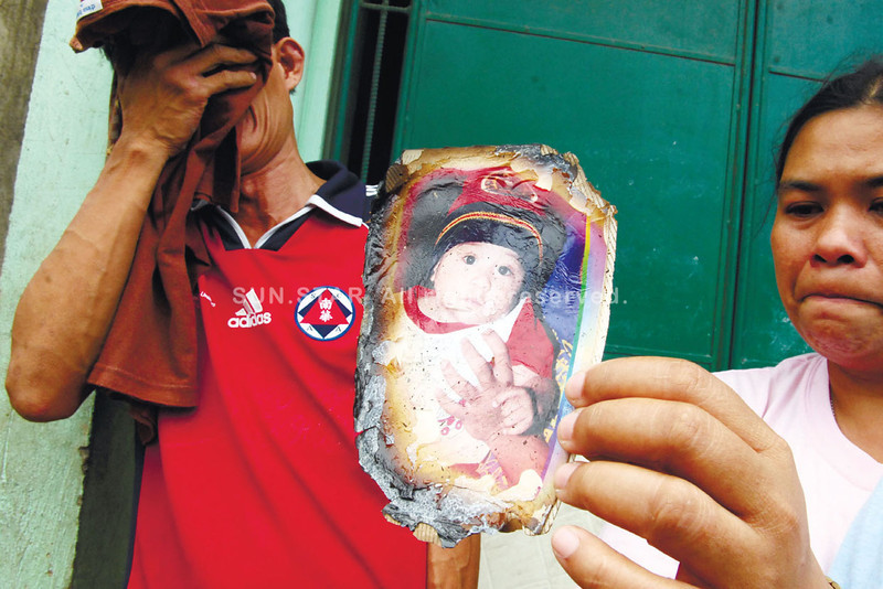 Grieving parents. Couple Eliseo and Rosella Tisoy show the photo of their three-year-old child Mark Lester who died when a fire broke out in their house in Sitio Hawod, Barangay Bulacao, Talisay City last Monday. Mark Lester's twin brother, Mark Anthony, survived the tragedy. (Alex Badayos)