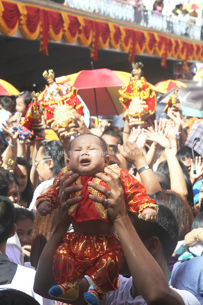'SUFFER THE LITTLE CHILDREN TO COME UNTO ME.' Perhaps overwhelmed by the crowd, a young participant in the Children's Mass at the Basilica del Sto. Niño briefly cries while being held above the heads of the crowd. (Sun.Star Photo/Alex Badayos)