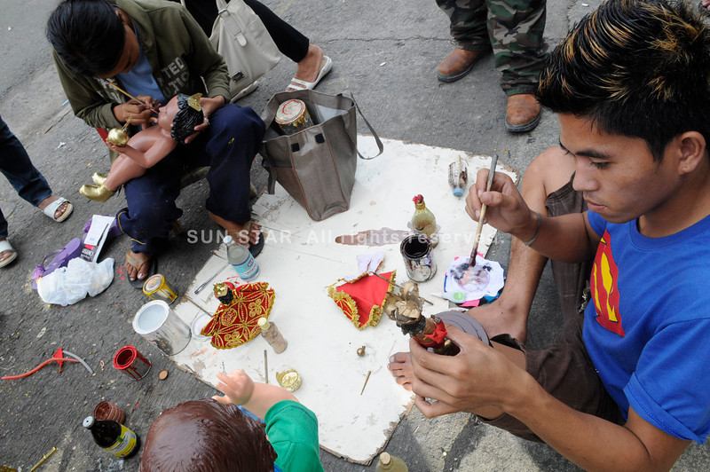 RETOUCH. Craftsmen set up roadside workshops to repair Sto. Nino icons. All sorts of small businesses come out during the Sinulog festivities with domestic and international visitors arriving in Cebu City. (Sun.Star photo/Allan Cuizon)