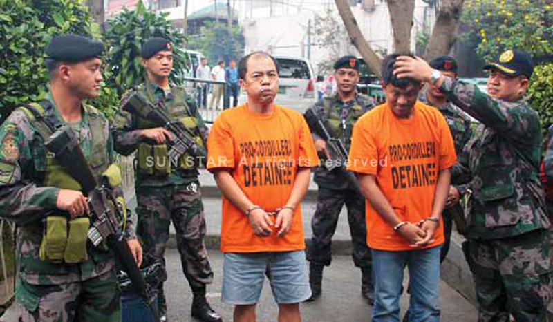 BAGUIO. Detainee Julio Bedking (left) and another arrested gang member, are presented to media by officers of the Baguio City Police Office. Bedking was tagged as the mastermind of the notorious acetylene gang. (Mauricio Victa)