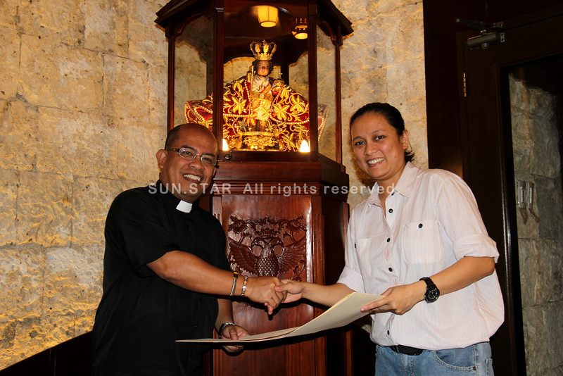 CEBU. Basilica del Santo Niño Church rector Fr. Jonas Mejares and Sun.Star Network Exchange acting editor-in-chief Mildred Galarpe shake hands after the signing of the partnership agreement on January 8, 2013 for the live streaming of the nine-day novena masses. (Mariz Puyo/Sunnex)