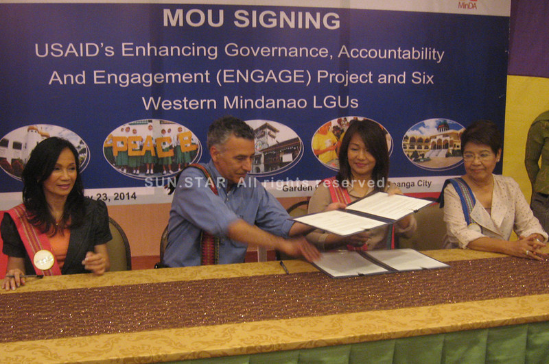 ZAMBOANGA. U.S. Ambassador Philip Goldberg and Lamitan City Mayor Rosita Furigay exchange copies of the agreement they sign Thursday witnessed by USAID-Philippines Mission Director Gloria Steele (left) and MinDA Chair Luwalhati Antonino. (Bong Garcia)