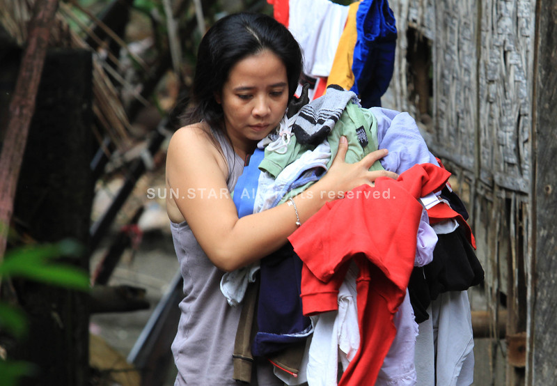 A happy day for this woman whose laundry dries up as the sun shines and the skies clear up in Linamon, Lanao del Norte on Thursday, January 23, 2014. (Richel V. Umel)