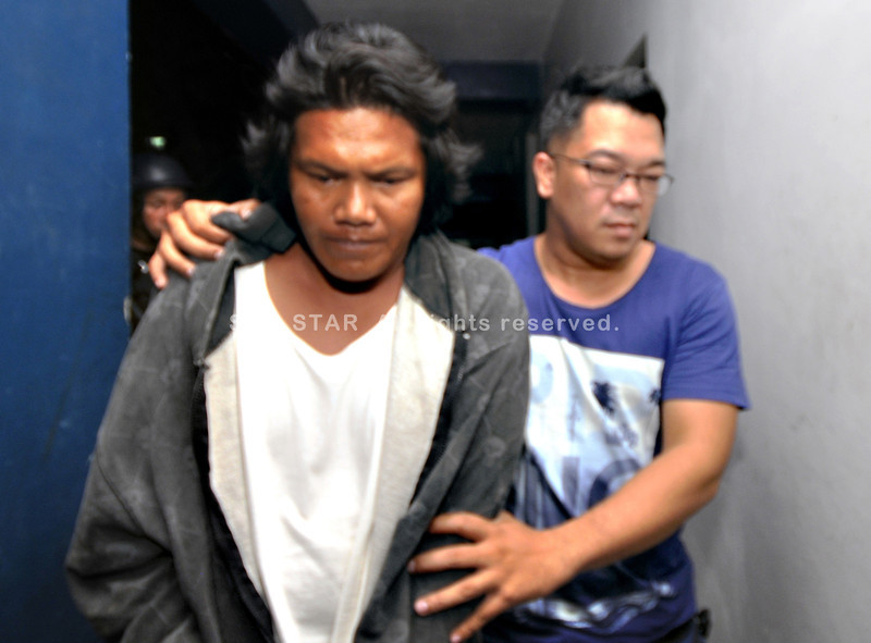 CEBU. An operative of the Regional Intelligence Division (RID) Central Visayas tightly escorts Junjun Cabando as they arrive from Zamboanga del Norte. Cabando, or Dionesio Cabatingan as he is also known, is said to be the leader of the group of robbers that pulled a daylight heist at Robinsons Place on September 5, 2011. (Alex Badayos)