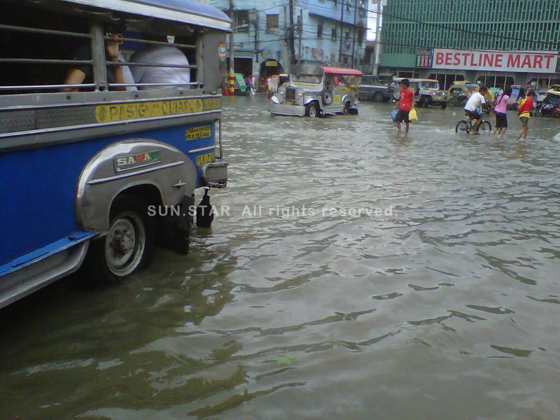 MANILA. People wade through ankle-deep water in Quiapo, Manila, on Wednesday morning after heavy rains spawned by southwest monsoon caused flooding in Metro Manila and nearby provinces. The inclement weather prompted school officials Wednesday to suspend classes anew. (Jill Beltran/Sunnex)