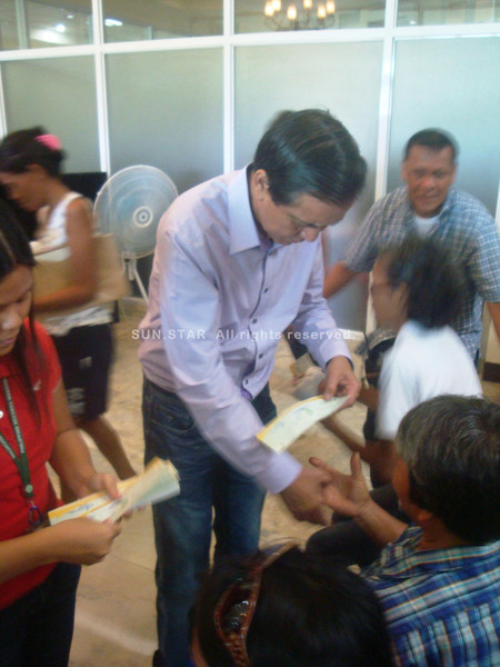 Cebu City Mayor Mike Rama distributes burial assistance
