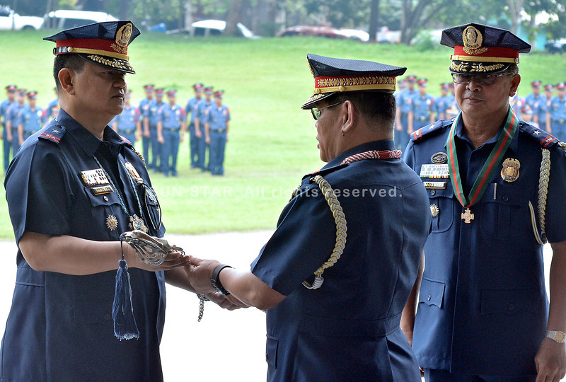 DAVAO. Acting regional police director Wency Pascual (left) receives the command symbol from PNP Chief Alan Purisima after it was handed over to him by outgoing regional director Jaime Morente (right) who relinquished his post in Thursday's turnover ceremony at Camp Quintin M. Merecido in Catitipan, Buhangin. (King Rodriguez)