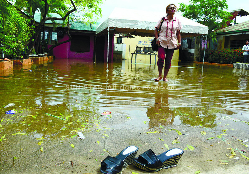 WALK ON WATER. Lourdes Buante, a Grade 4 teacher at the Cesar Cabahug Elementary School, wades through the seawater that enters the school during high tide. Mandaue City will address the problem by building a riprap to prevent seawater from the school premises. (Allan Cuizon photo/Sun.Star Cebu)