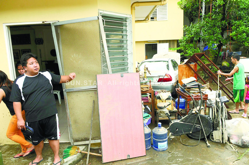 The residence of CITOM executive director Attorney Rafael Christopher Yap(left) in barangay Mabolo was flooded during Saturday's heavy rainfall leaving some properties damaged.        (SUNSTAR FOTO/ARNI ACLAO)