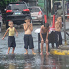 Children play in the flood caused by a heavy rain showers Wednesday, along Junquera Street, Cebu City.