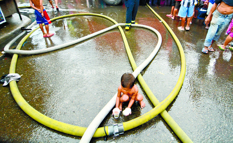 A child in Alaska Mambaling tries to get water from the connectiong fire hose during a fire in the area several houses were gutted by early dawn fire.<br /> foto: Alex badayos