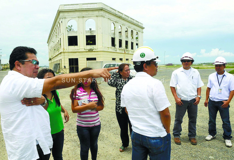 BOUNDARY ISSUES WITH CITY HALL. Cebu Port Authority deputy general manager Yusoph Uckung (left) points to boundaries of the land surrounding the Compañia Maritima building (background) during an inspection with journalists. (Arni Aclao photo/Sun.Star Cebu)
