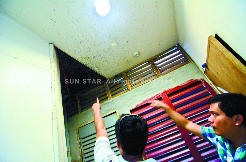 HIDEOUT. Gesim Nacario (right), chief security offi cer of Gaisano Fiesta Mall in abunok,Talisay City, shows police a gap in the ceiling where a suspected thief accesses his hideout. (Alex Badayos photo/Sun.Star Cebu)