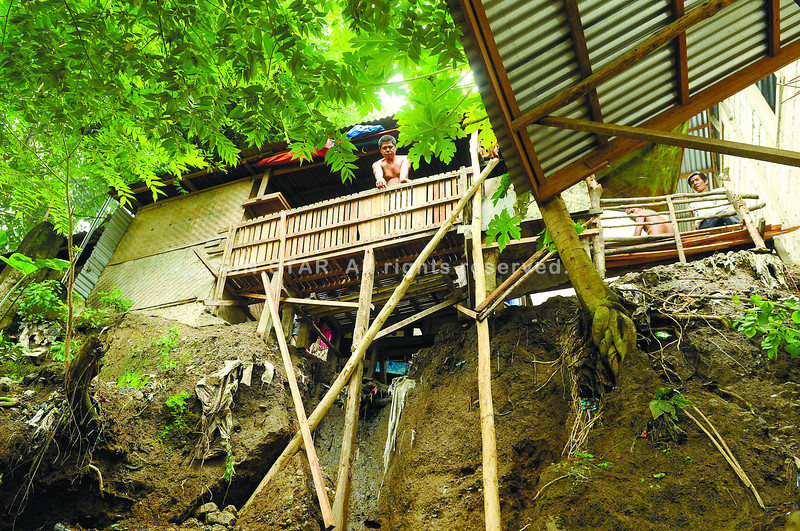 A soil erosion in sitio OPRRA, barangay Kalunasan leaves a portion of a house hanging after Saturday's heavy rainfall.      (SUNSTAR FOTO/ARNI ACLAO)