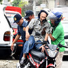 Policemen help old man ride motorcycle