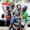 Policemen help old man ride motorcycle