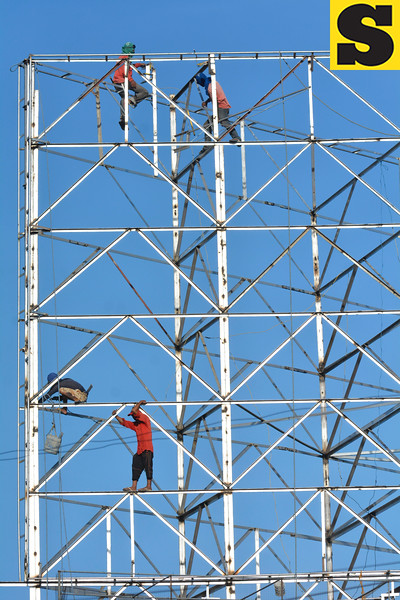 Workers fixing a large billboard frame