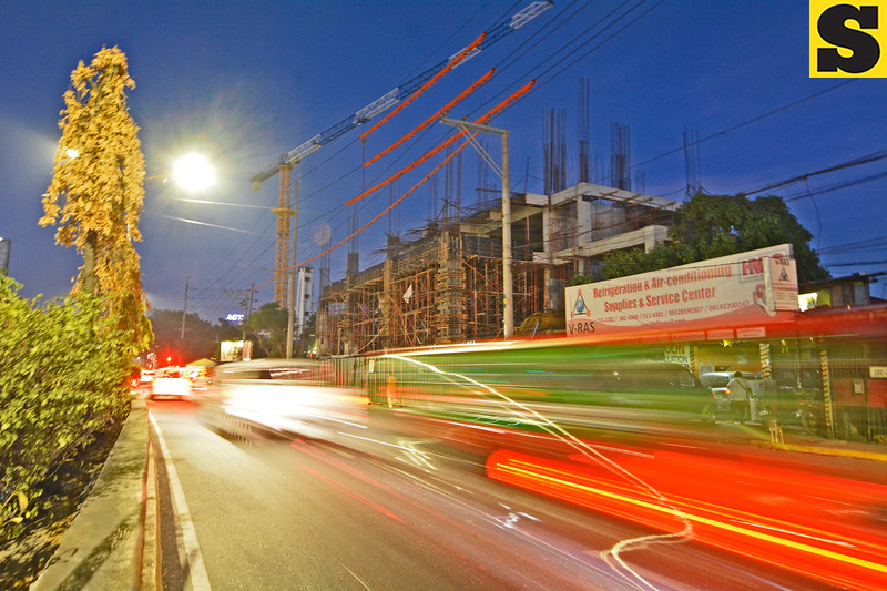 Speeding vehicles pass by the Cebu City Medical Center's ongoing structure