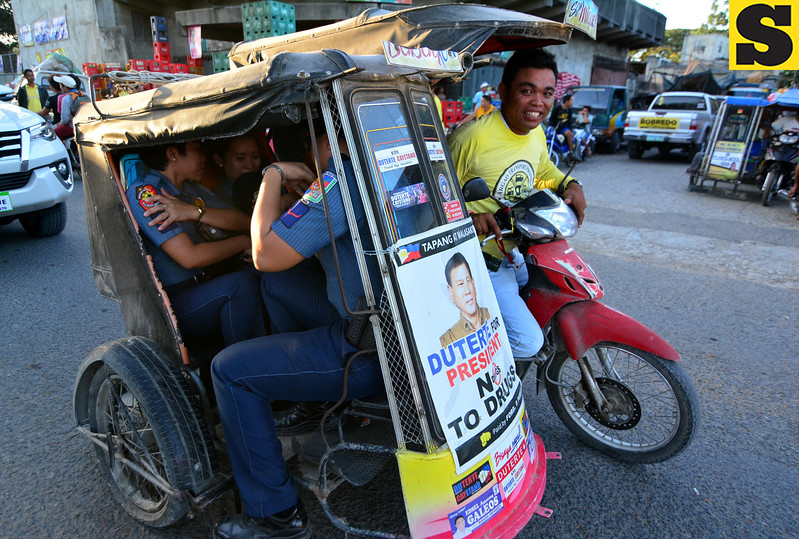 Police officers inside a tricycle