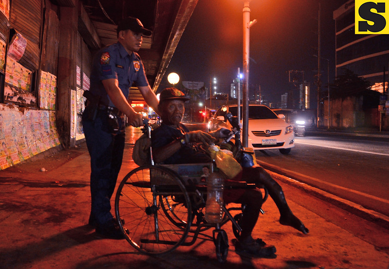 Policeman assists old man on wheelchair
