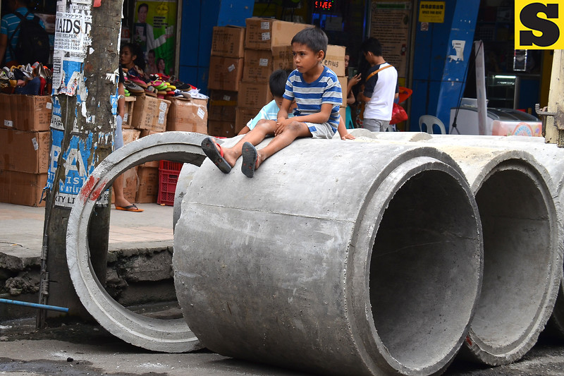 Boy sits on cement culvert