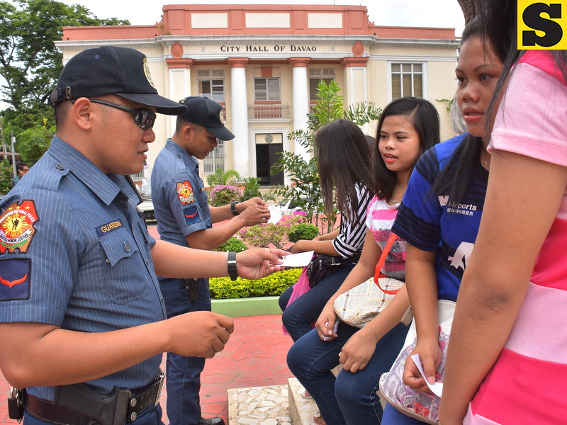 Davao police distribute fliers of police hotline numbers