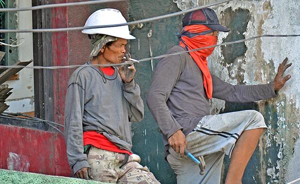 Construction worker smokes cigarette