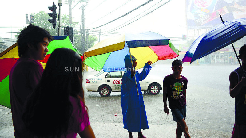RAINY DAY SERVICE. PUJ dispatchers and ambulant vendors found an opportunity to make money<br /> during rainy days: they offer the temporary shelter of an umbrella for P5 to pedestrians who<br /> want to cross the street in Barangay Mabolo, Cebu City. (Allan Cuizon of Sun.Star Cebu)