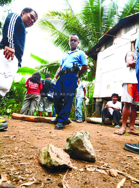 Talisay police (left) found rocks with bloodstains just outside the Labitad hut in Camp 4, Talisay City but not the body Warren Labitad. (Alex Badayos photo)
