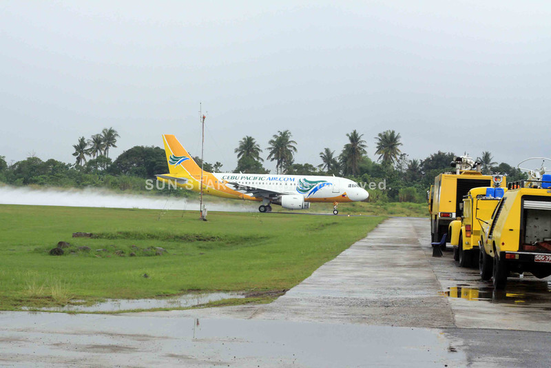 caution in the wind - a Cebu Pacific plane's take off generated water stream in its wake after a heavy downpour at the Lumbia Airport on Wednesday as three airfield fire fighting vehicles are parked on its access way. airport safety and response time went under scrutiny after the Cebu Pacific plane skid off the runway in Davao City on Sunday night after a heavy downpour. The Fire Crash Rescue Unit (FCRU) of the Civil Aviation Authority of the Philippines stationed at the airport said that it is capable of responding within three minutes after an emergency call within the airport, a far cry to the percieved slow response in the Davao accident. (bobby lagsa)