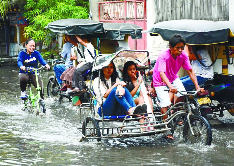 EXTRA TRIPS DRAIN WALLETS. Flood in a street leading from Barangay Poblacion to Cansojong in Talisay City forces commuters to spend extra for the ride that will bring them to dry land and other means of transport. (Alex Badayos)